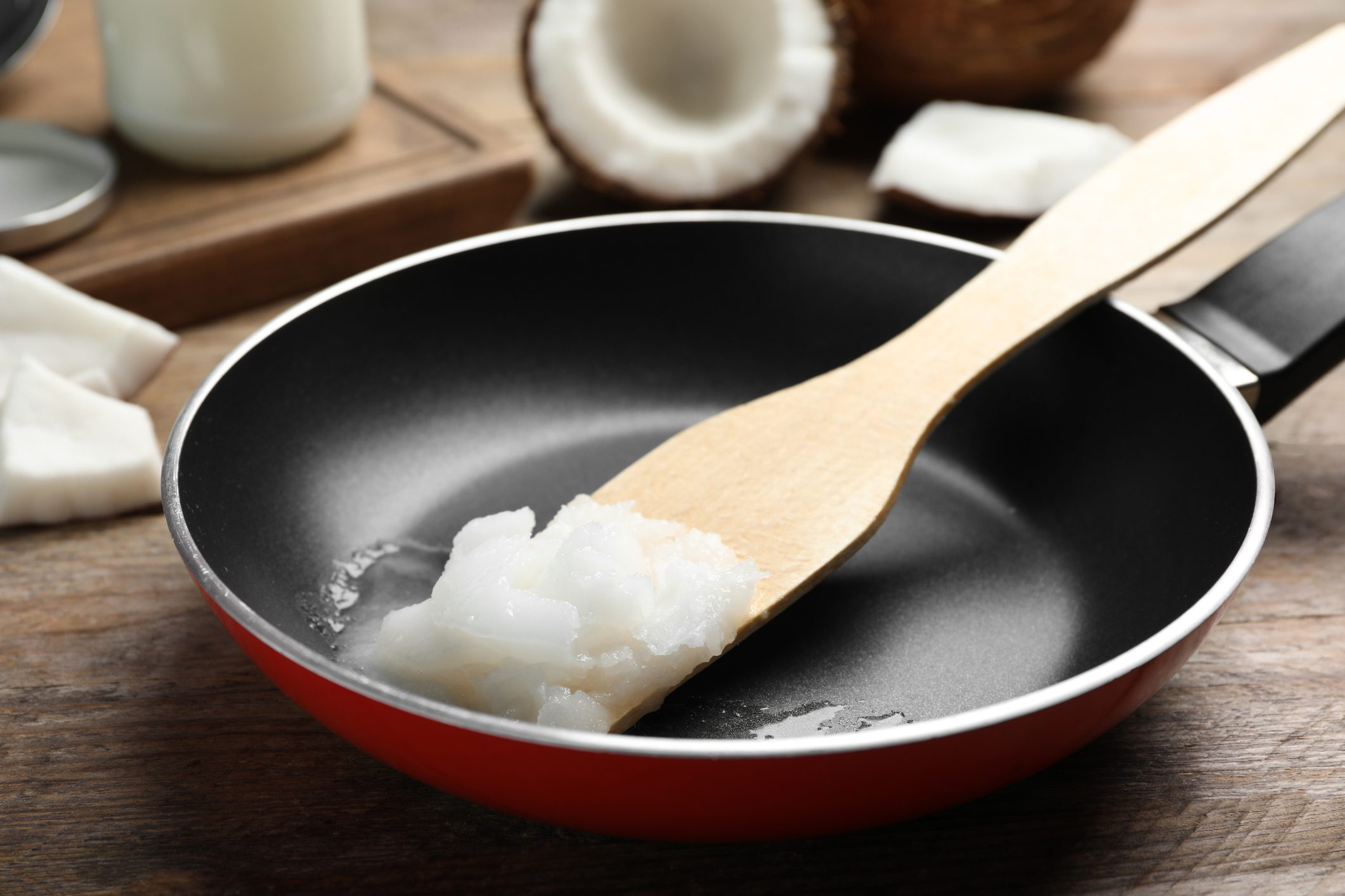 healthiest cooking oils | Frying pan with coconut oil and wooden spatula