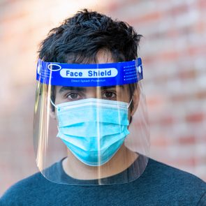Young man posing wearing a face shield and a protective mask looking at the camera against a brick wall