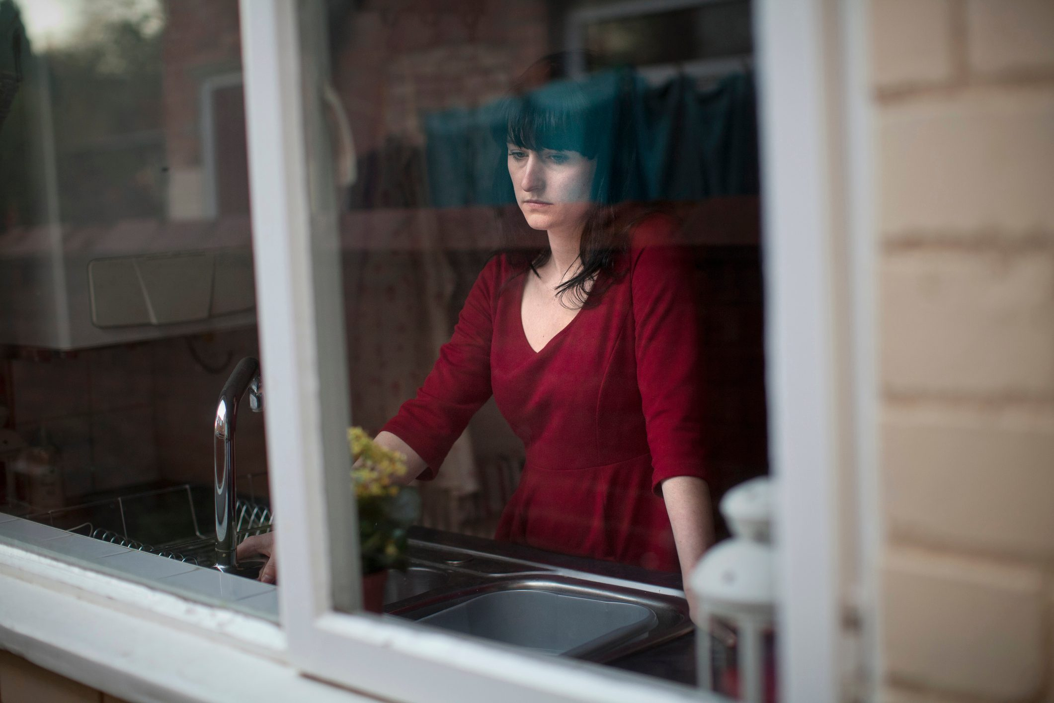 sad woman at kitchen sink, looking out window