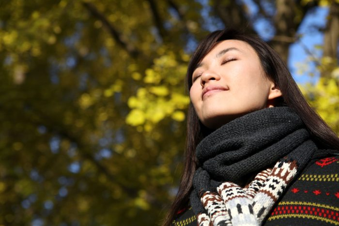 woman outside with eyes closed