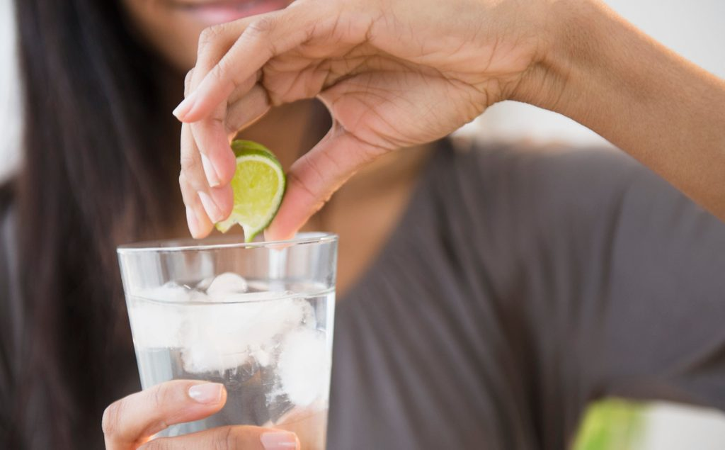 Mixed race woman squeezing lime into drink