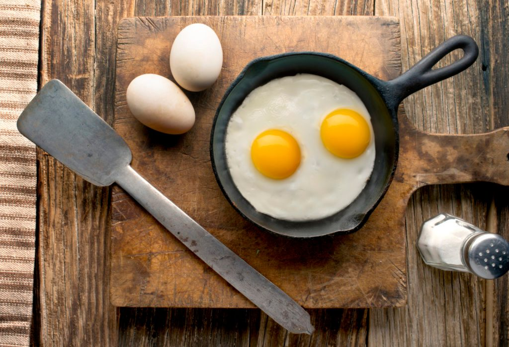 eggs in cast iron skillet on wood overhead