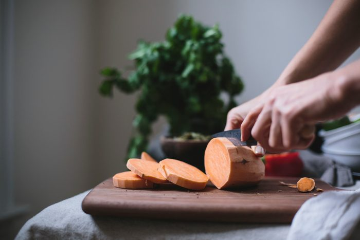 A woman is slicing a sweet potato to use in a sweet potato