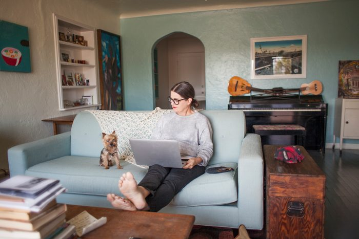 Woman sitting on couch with laptop computer
