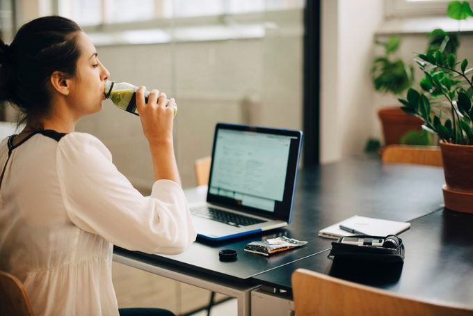 Businesswoman drinking juice while using laptop at desk in office