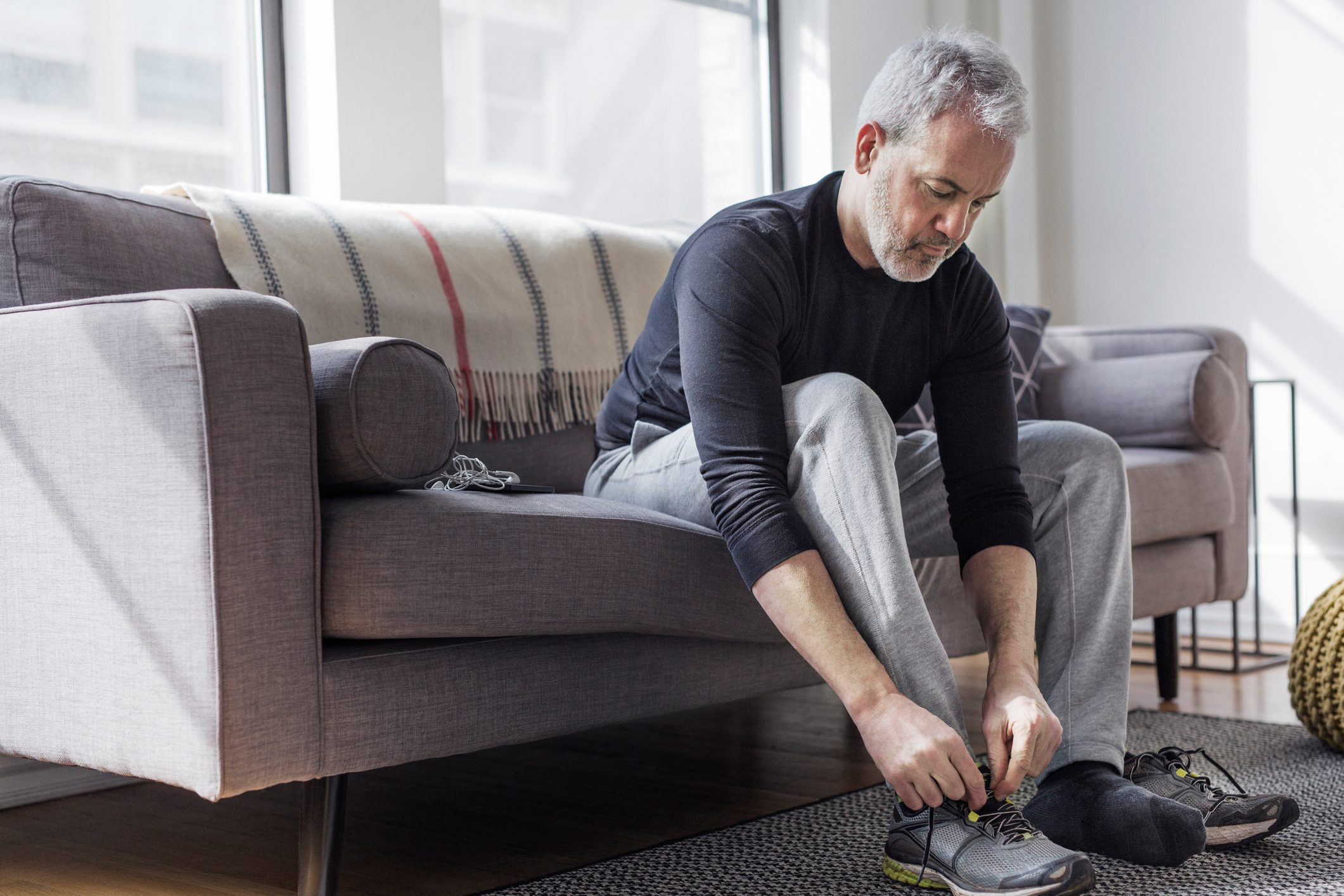 Full length of mature man wearing sports shoe at home