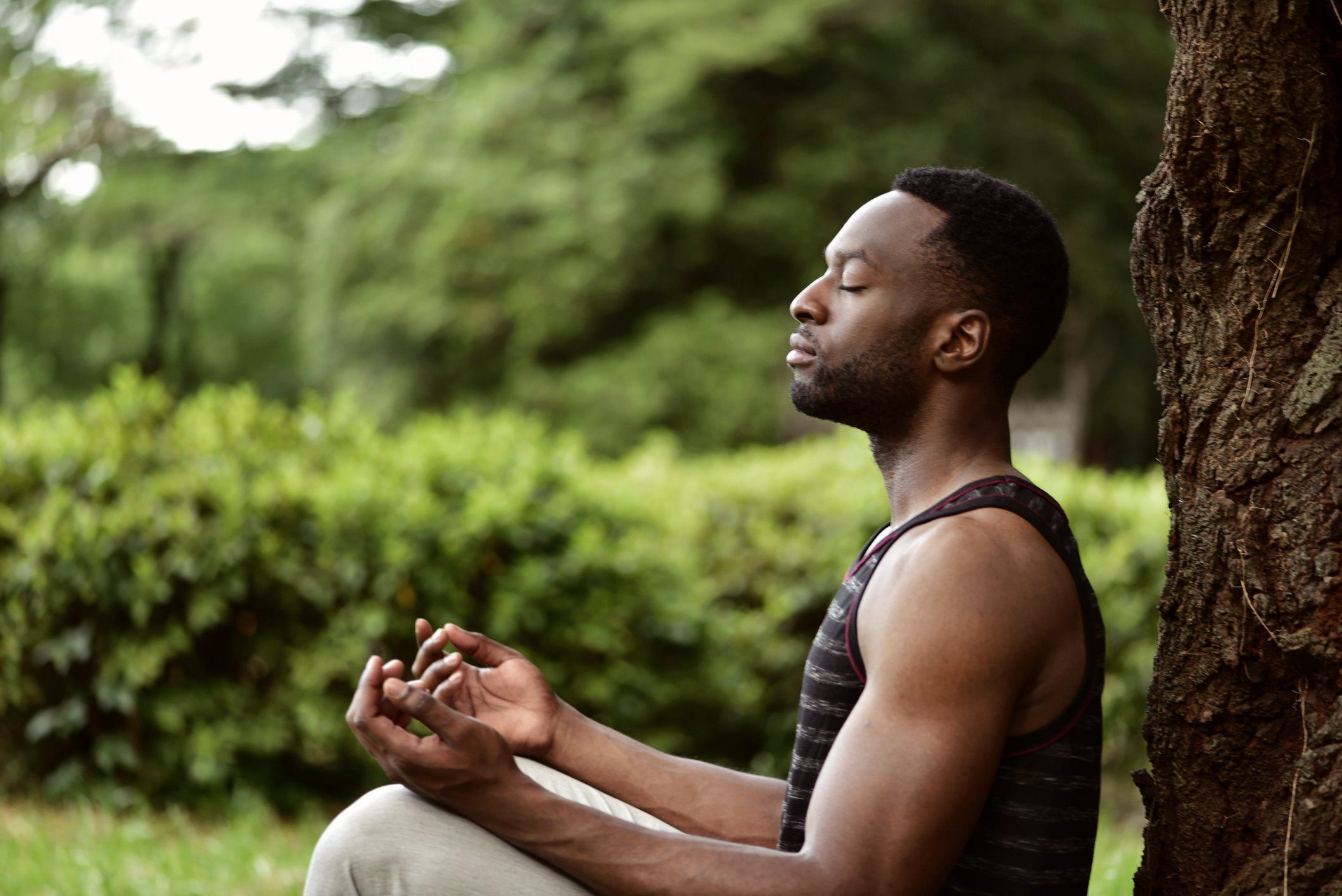 young man meditating outside under a tree