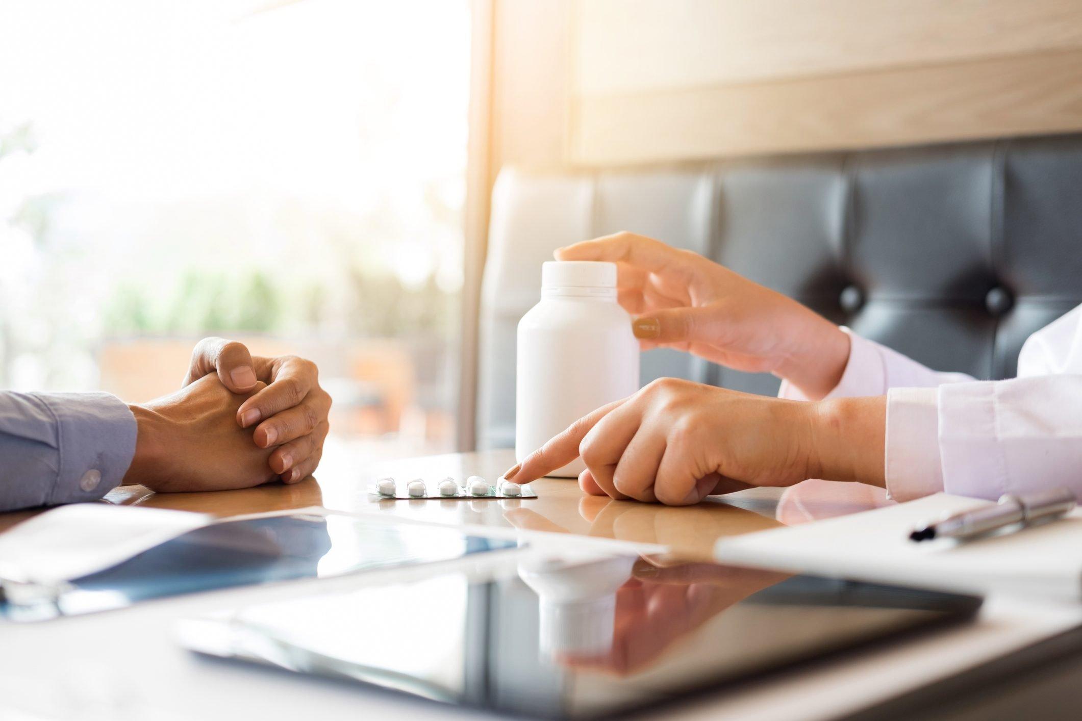Cropped Hands Of Doctor Prescribing Medicine To Patient On Desk