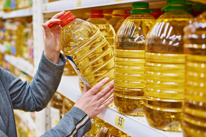 woman taking large bottle of oil off of shelf at grocery store
