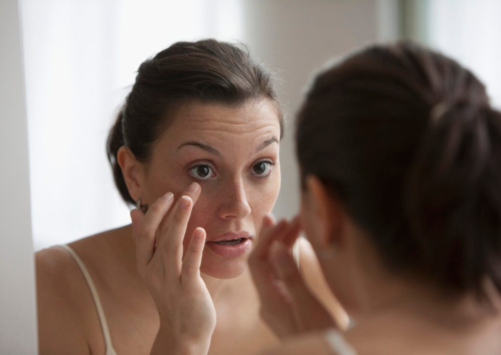 Young woman checking her eye in the mirror