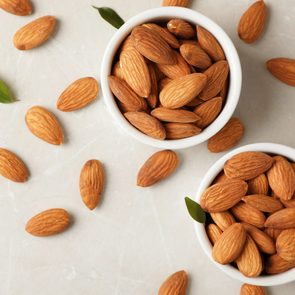 Tasty organic almond nuts in bowls and space for text on table, top view