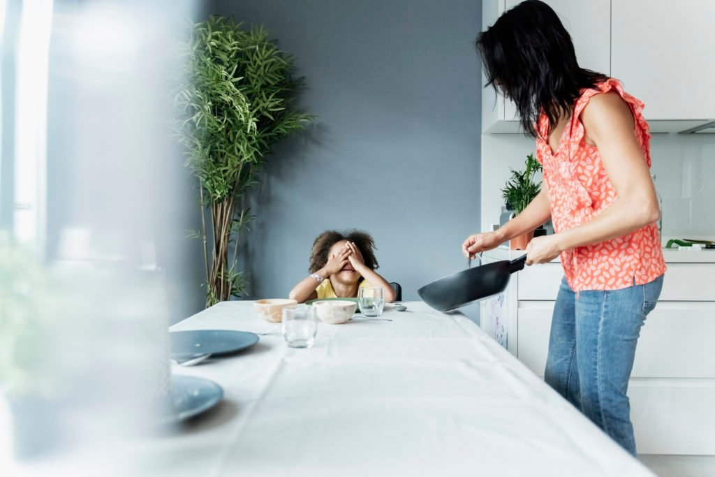 Mother serving meal for daughter sitting at dining table