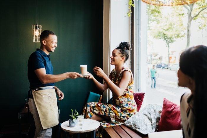 Barista Serving Customer Coffee