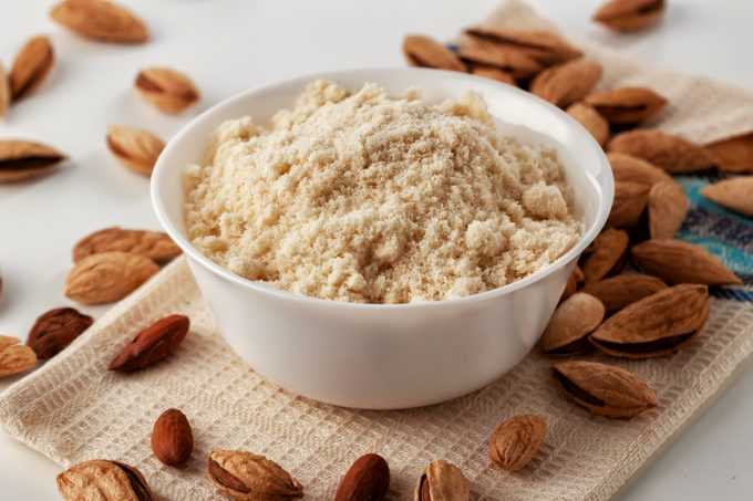 almond flour in white bowl with almonds on table