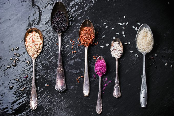 Directly Above Shot Of Various Rice In Spoons On Wet Slate