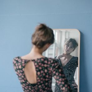 Young woman in vintage dress looking into mirror
