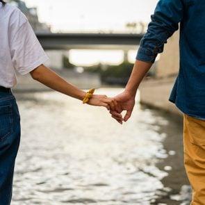 France, Paris, couple holding hands at river Seine
