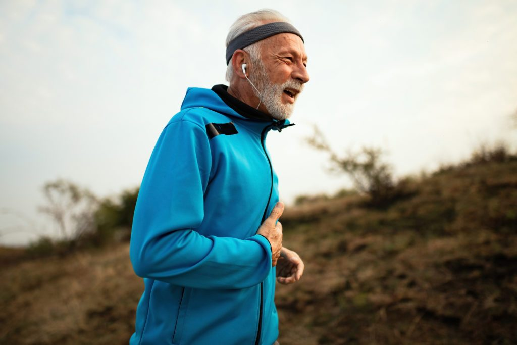 Senior runner experiencing pain while jogging in nature.