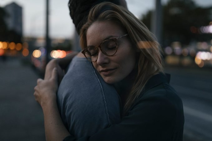 Young couple hugging in the city at dusk