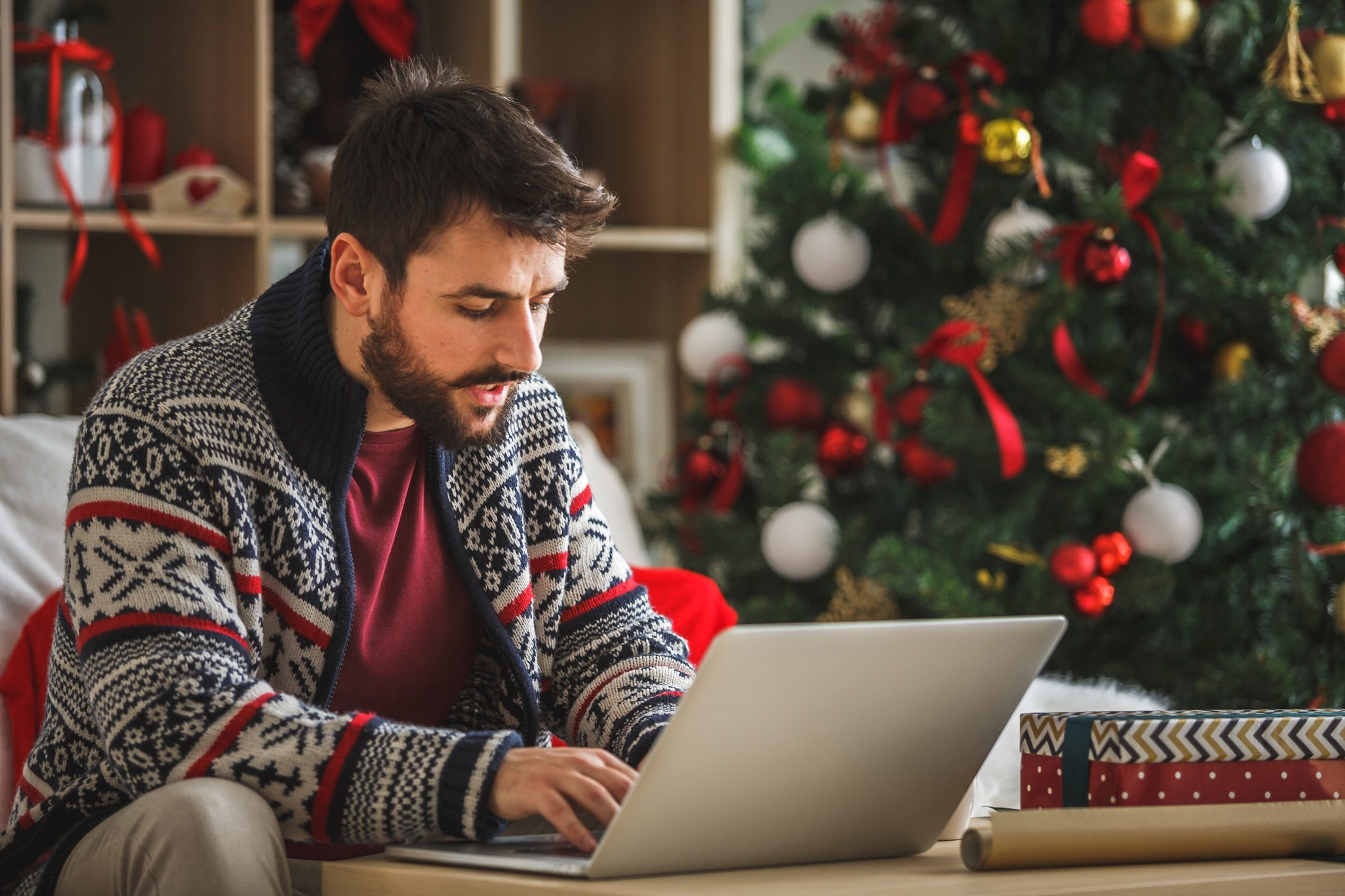Young man using laptop in the living room near the Christmas tree