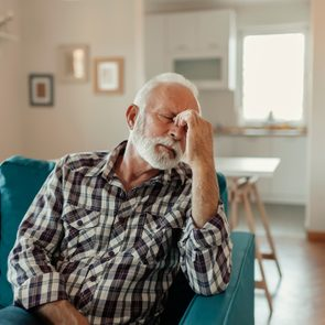 mature man with headache on couch at home