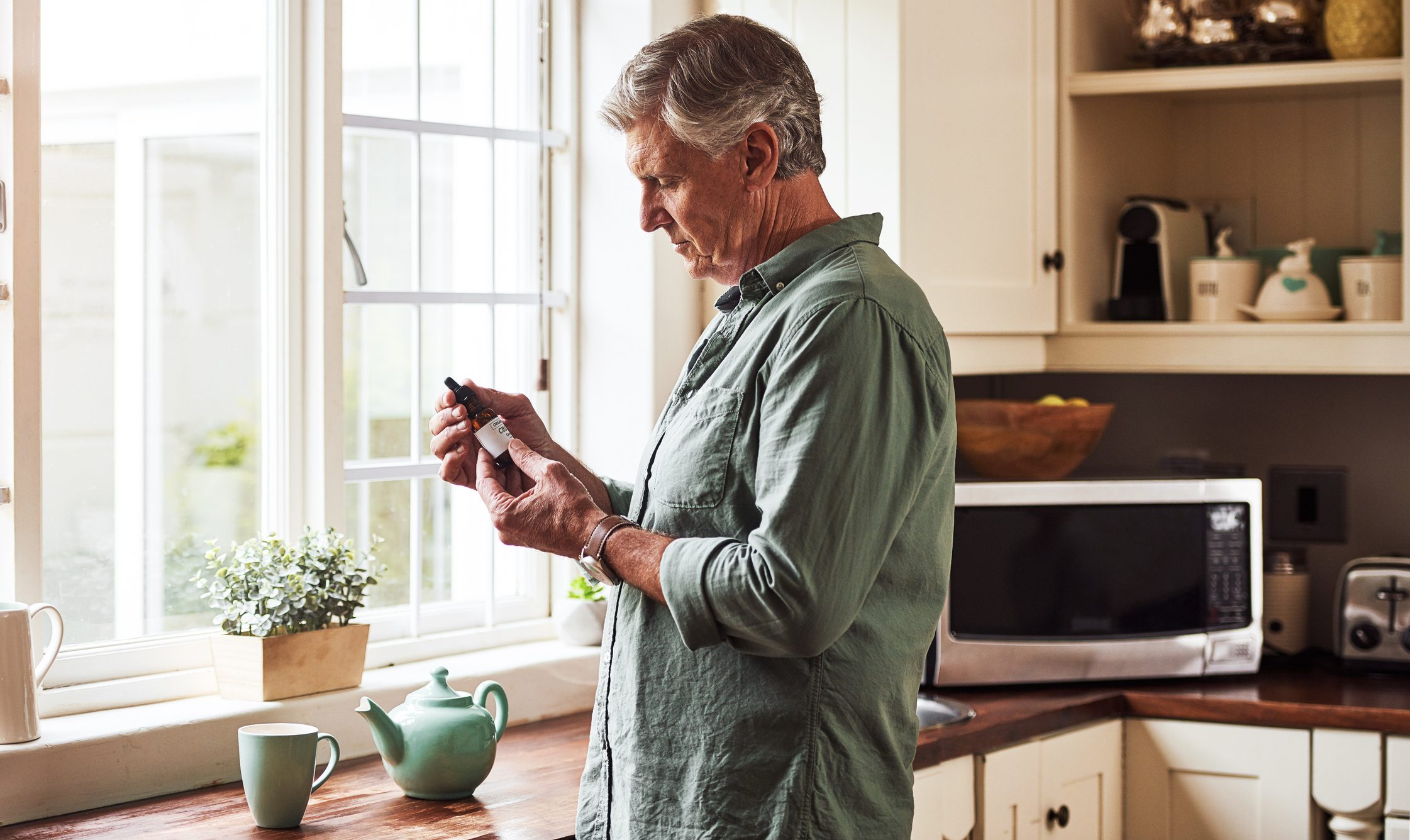 mature man holding bottle of CBD oil in kitchen