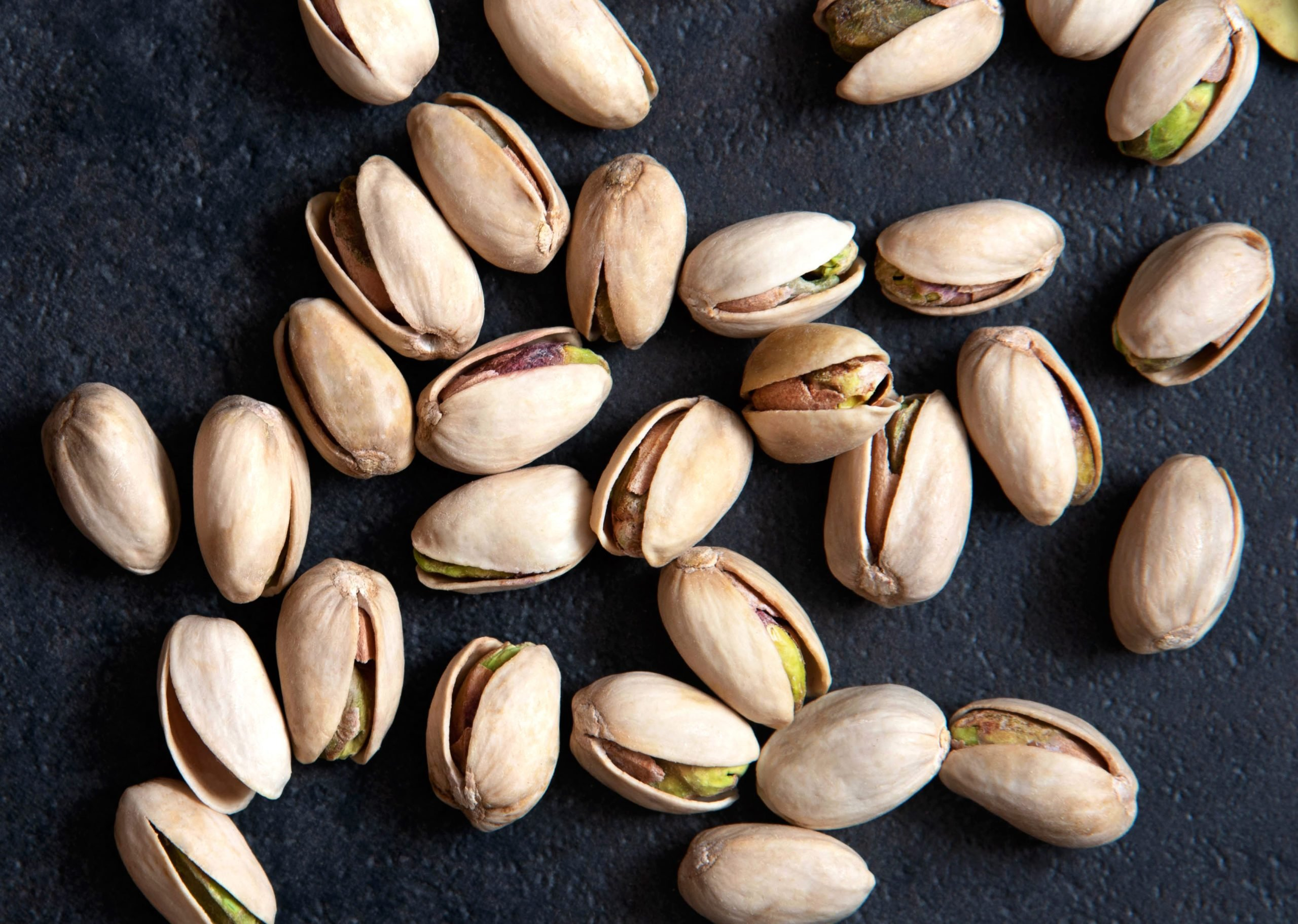 Roasted pistachios nuts on dark background