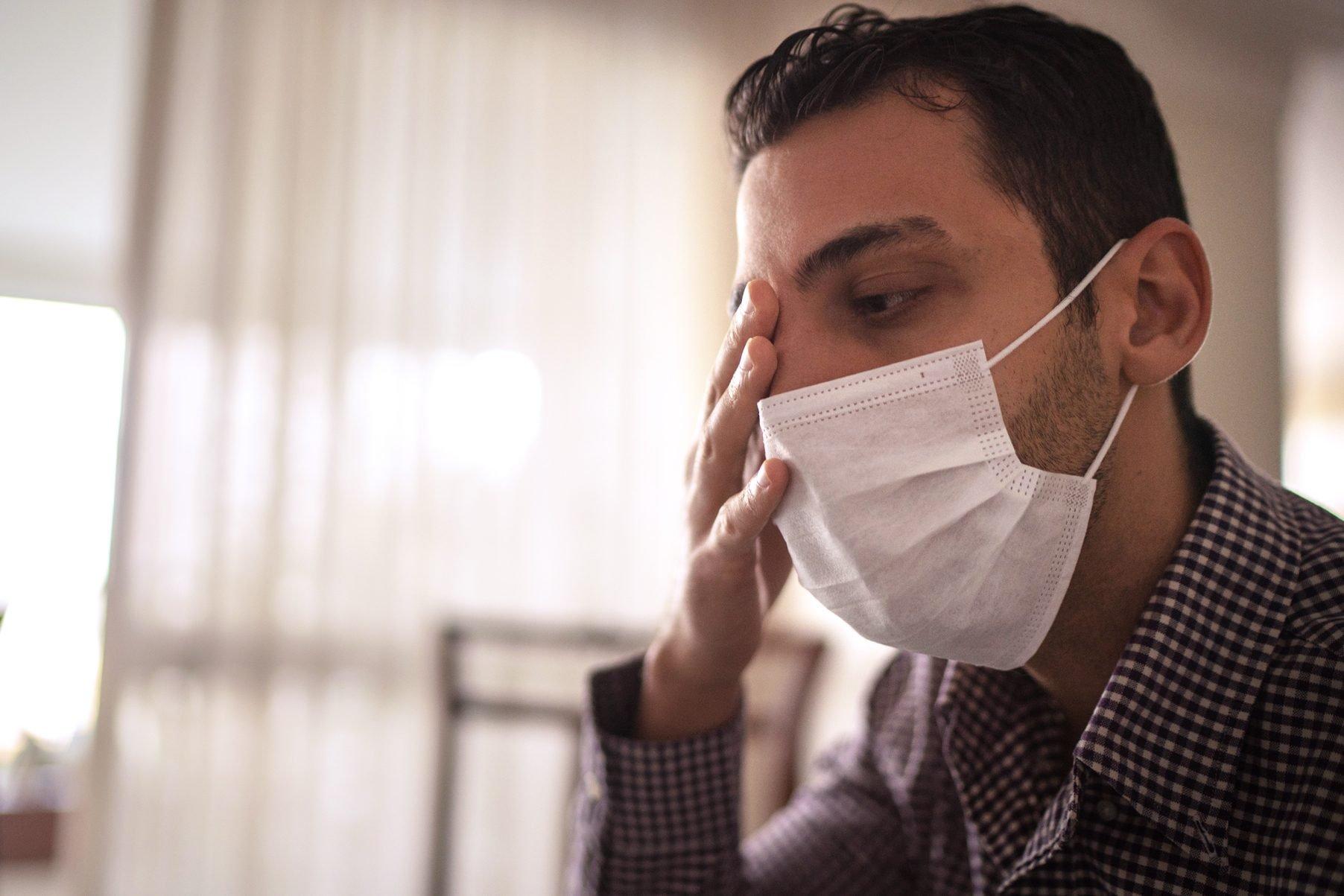 man wearing face mask and touching eye