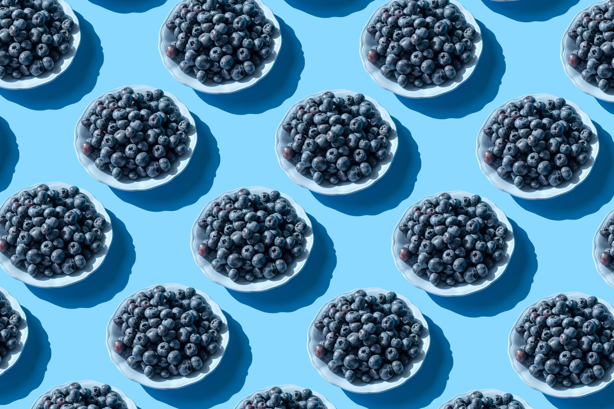 Blueberries on the plate on the blue background