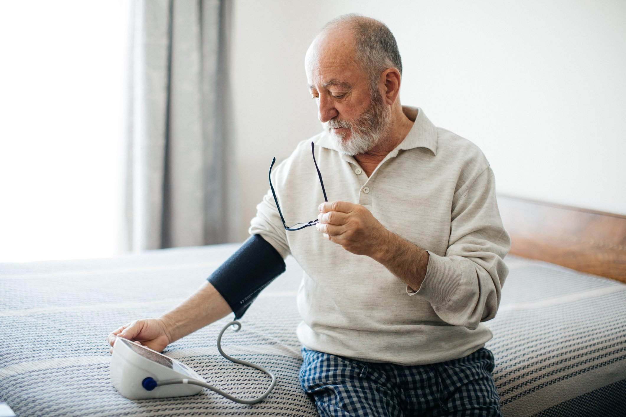 Active senior man measuring blood pressure with sphygmomanometer in bedroom