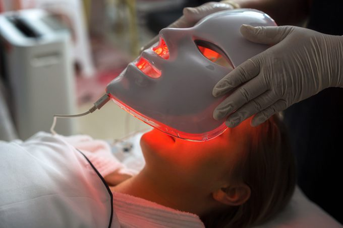Woman getting LED mask regenerative treatment at the facial spa.