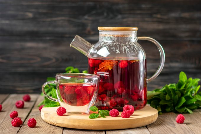 Herbal tea with berries, raspberries, mint leaves and hibiscus flowers in glass teapot and cup on wooden table Medicine for cold Vitamin drink Rustic style
