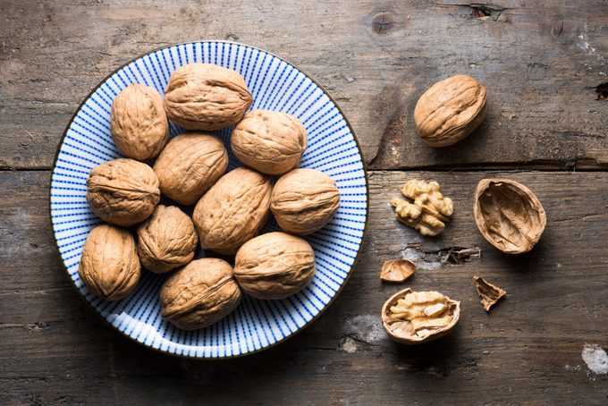 Overhead bowl of walnuts on a rough wooden background