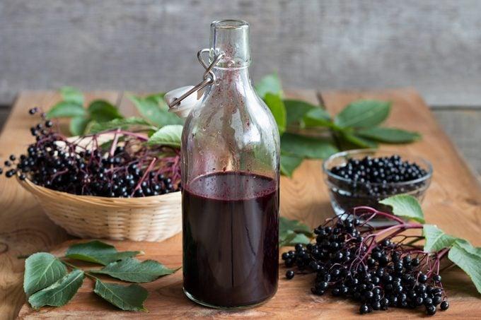 A bottle of elderberry syrup and elderberries