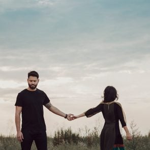 Couple in field holding hands