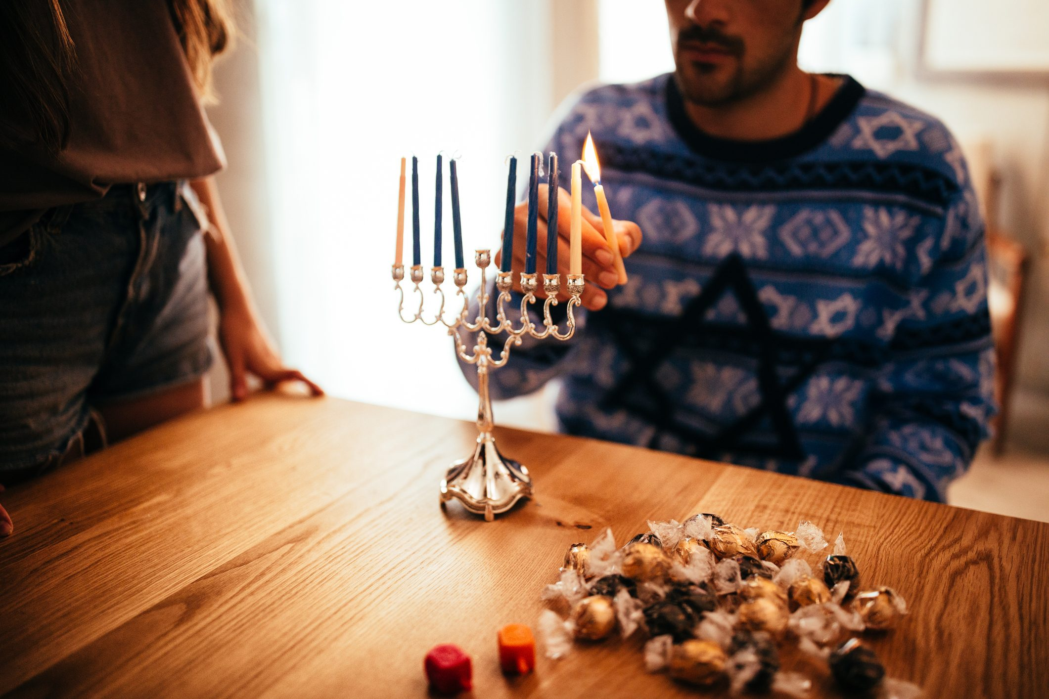Young man lighting candlesticks on traditional jewish menorah for Hannukah