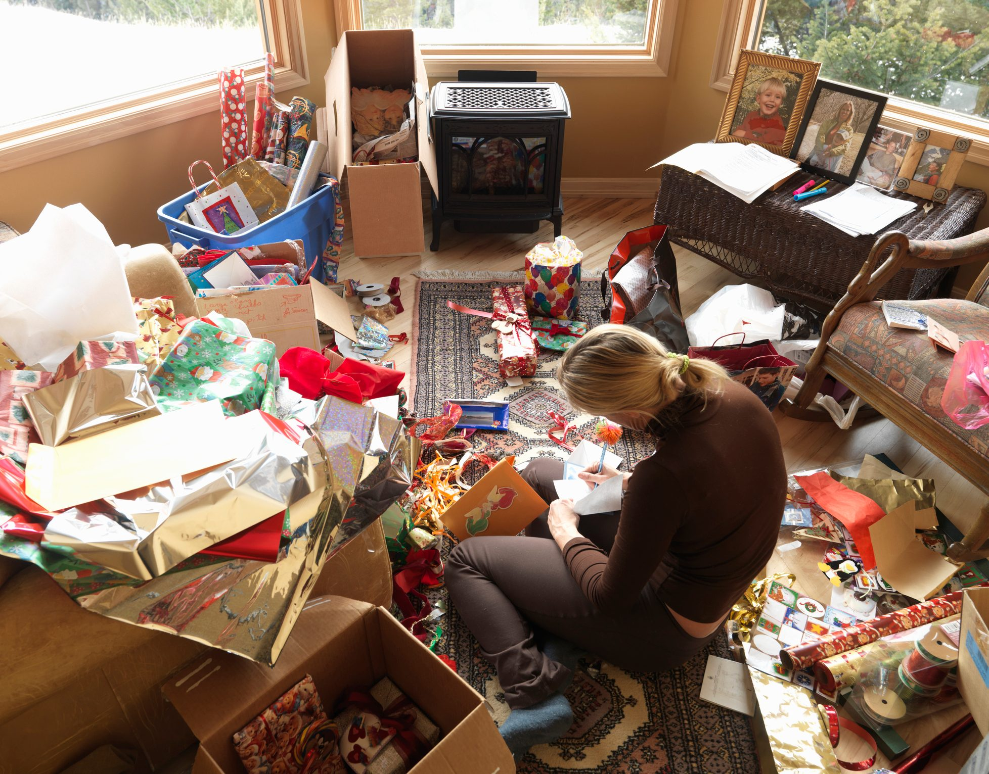 Woman sitting in living room writing on Christmas cards, elevated view