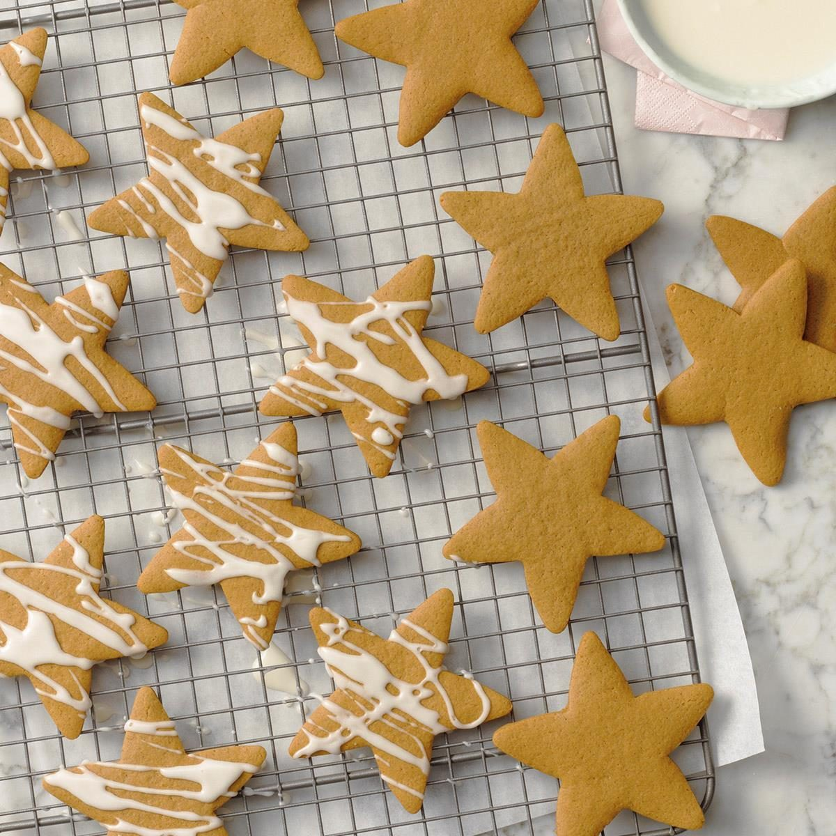 A wire rack with star-shaped cutout cookies cooling before they get drizzled with icing.
