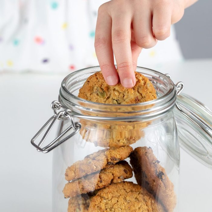 Clear glass jar full of cookies, child's hand taking one of the cookies out of the jar.
