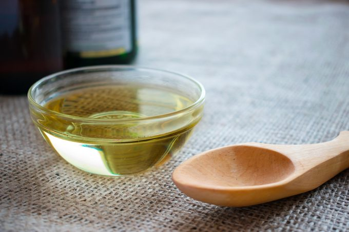 Liquid coconut MCT oil in round glass bowl with wooden spoon and bottles. Health Benefits of MCT Oil. Triglycerides, a form of saturated fatty acid.