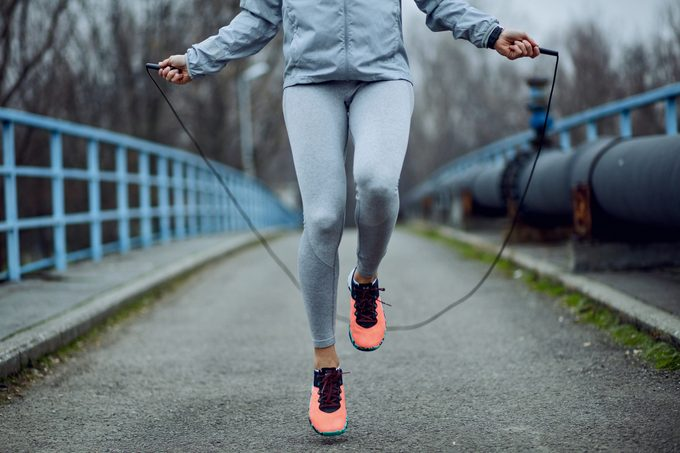 woman jumping rope on a bridge.