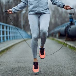 Unrecognizable sportswoman jumping rope on a bridge.