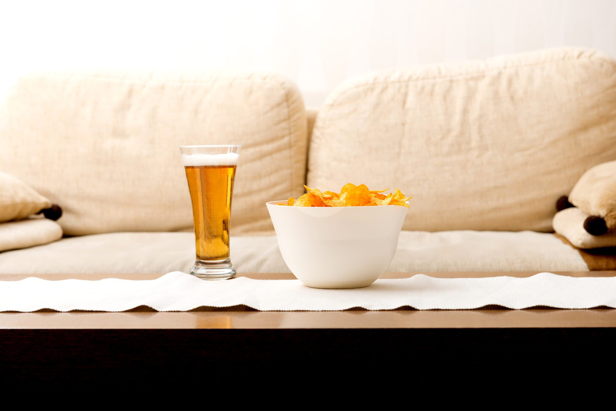 Close-Up Of Beer And Snack In Bowl On Table At Home