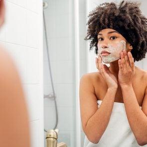 Teenage Girl Applying Facial Mask While Looking In Mirror At Bathroom