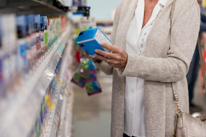woman shopping for medication in pharmacy