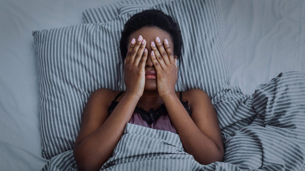 woman with closed eyes with hands in bed