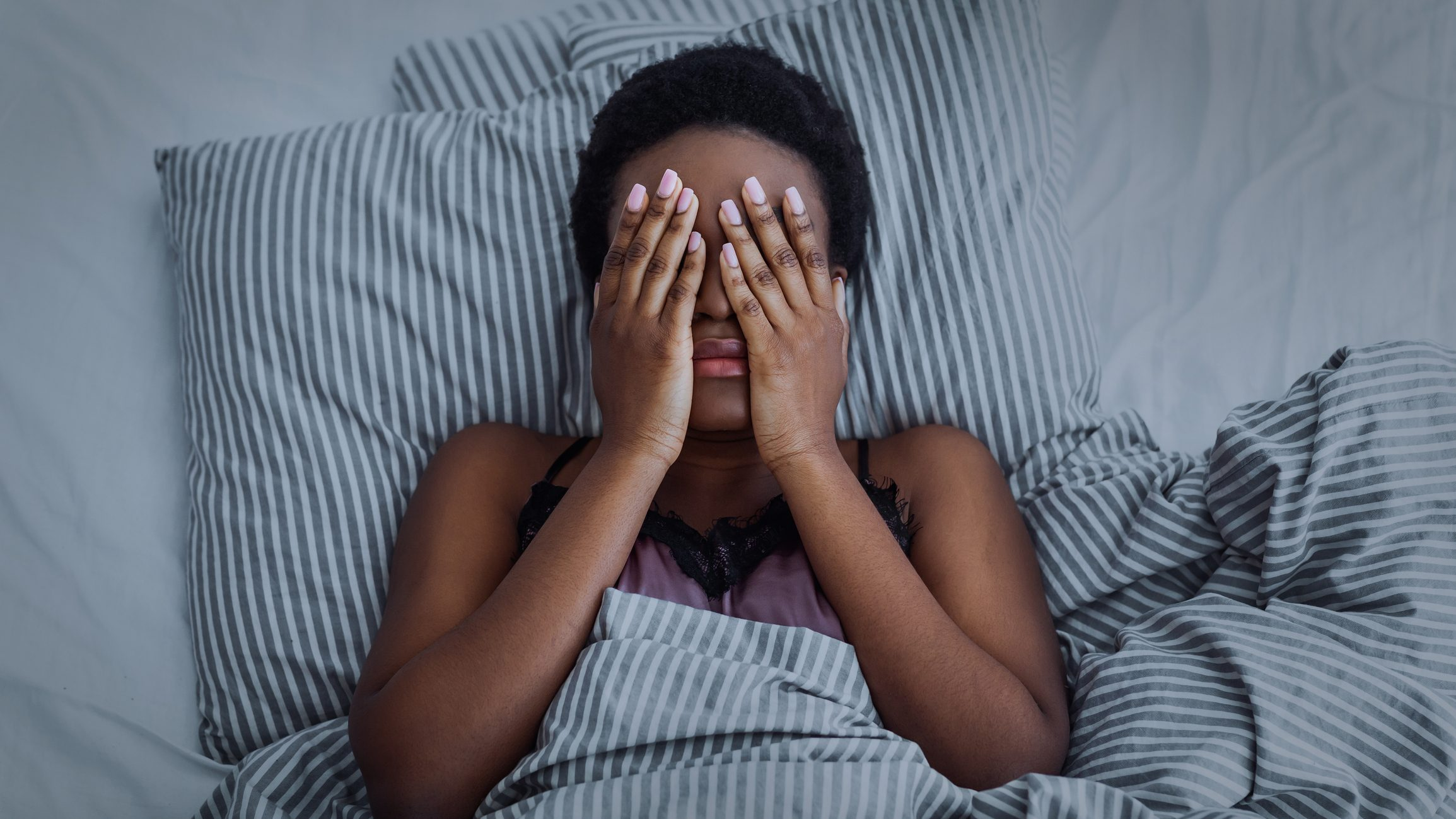 African american girl closed eyes with hands in bed