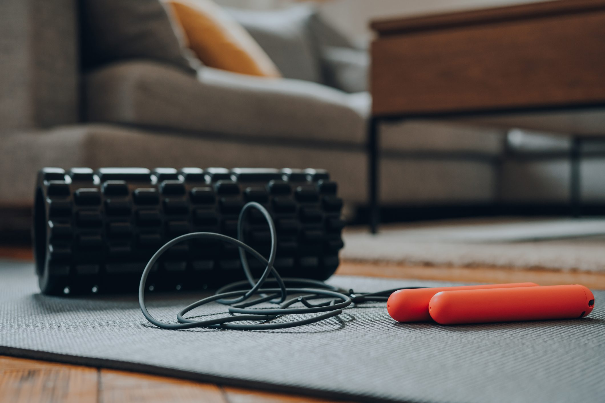Close Up Of A Jump Rope And A Foam Roller On A Fitness Mat