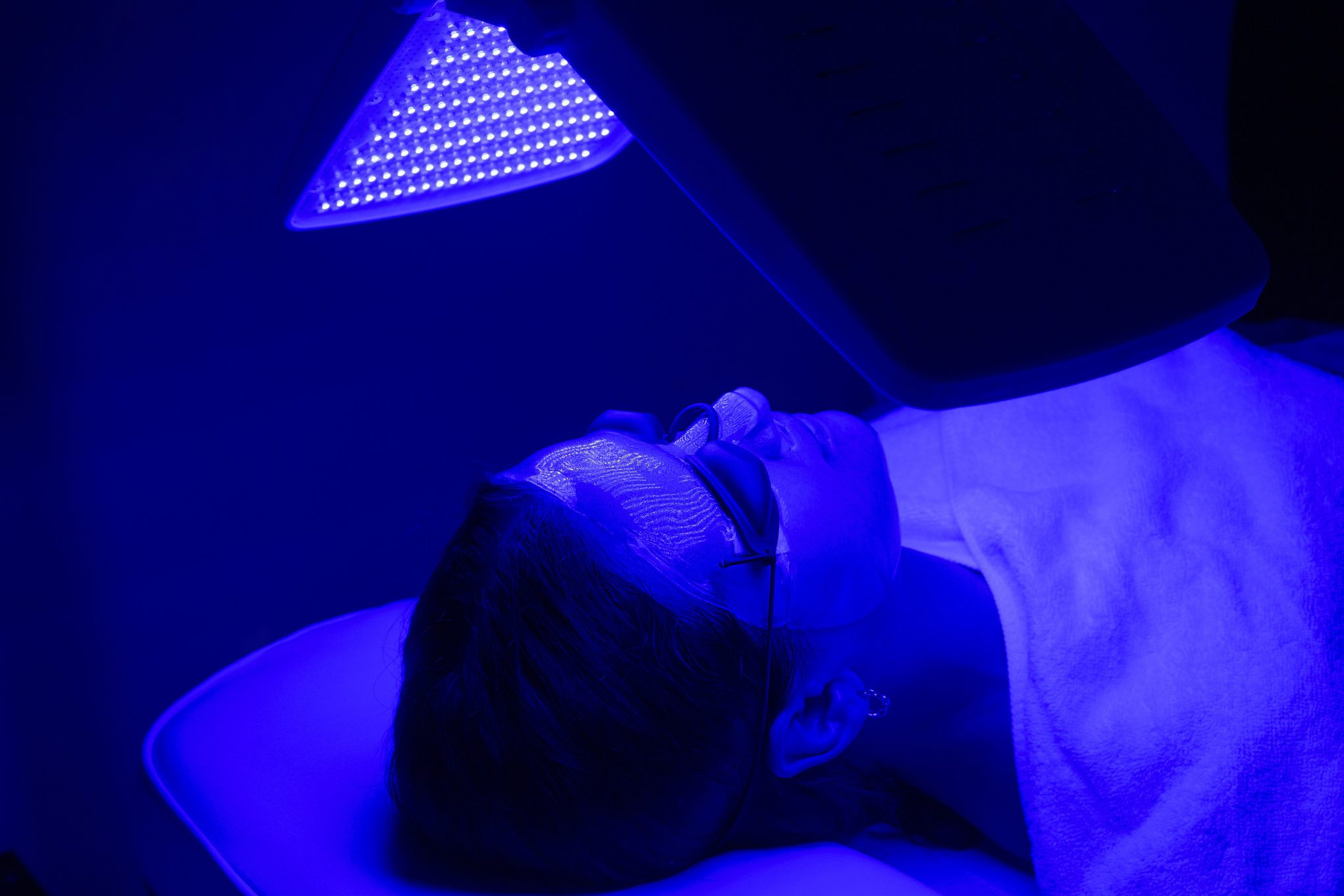woman having blue LED light facial therapy treatment