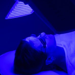 Young woman having blue LED light facial therapy treatment in beauty salon. Beauty and wellness